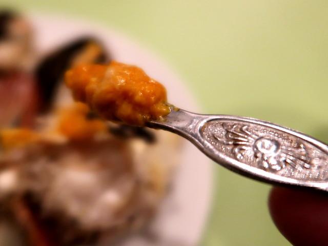 甲羅の味噌を掬って食べる